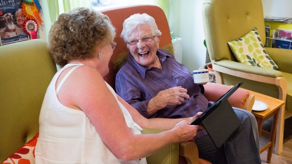 Volunteer with lady laughing with iPad
